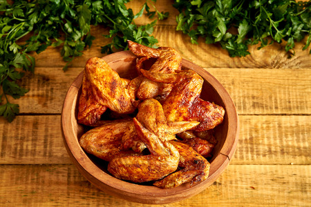 Delicious grilled chicken wings in wooden bowl with parsley on wooden table.