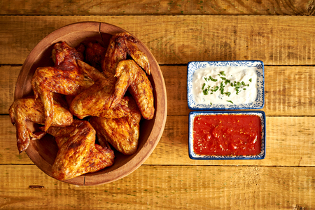 Delicious grilled chicken wings in wooden bowl with dips to choose from on wooden table. Фото со стока