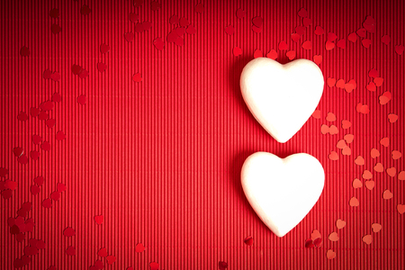 Valentines Day background with red ribbed paper with two white foam hearts for lovers Stock Photo