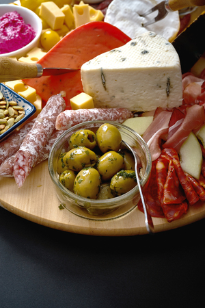 Antipasti board with various cheese and meat snacks with hummus and olives on wooden round board