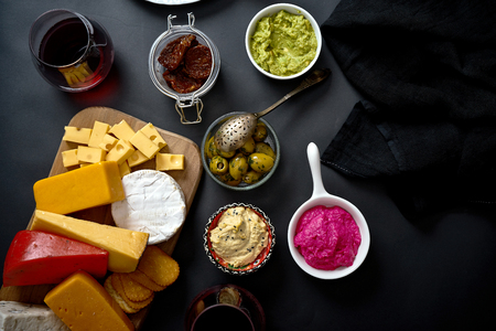 Wooden board with various types of cheese and snacks and two glasses of red wine on black table Stock Photo