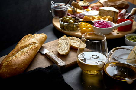 Antipasti board with cheese and meat snacks with white wine and baguette on board on black table Stock Photo