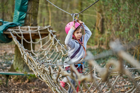 Adorable little girl in helmet in rope park in forest Stock Photo - 125295689