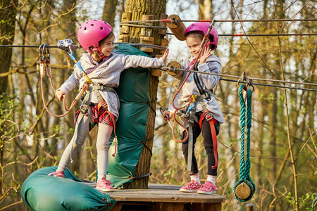 Two adorable little girls in helmet in a rope park in the woods Stock Photo - 125295695