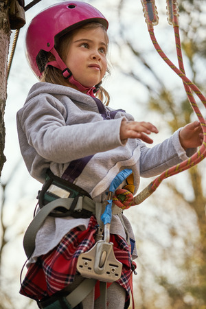 Adorable little girl in helmet in rope park in forest Stock Photo - 125295645