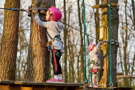 Two adorable little girls in helmet in a rope park in the woods Stock Photo - 125295704