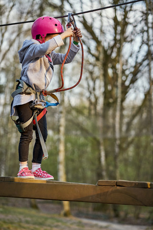 Adorable little girl in helmet in rope park in forest Stock Photo - 125295730