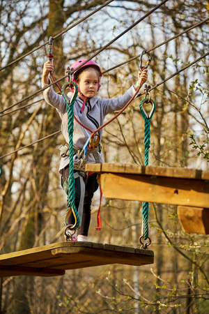 Adorable little girl in helmet in rope park in forest Stock Photo - 125295610