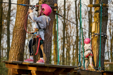 Two adorable little girls in helmet in a rope park in the woods