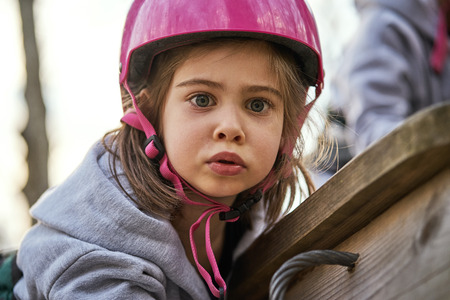 Adorable little girl in helmet at the playground Stock Photo - 125295618