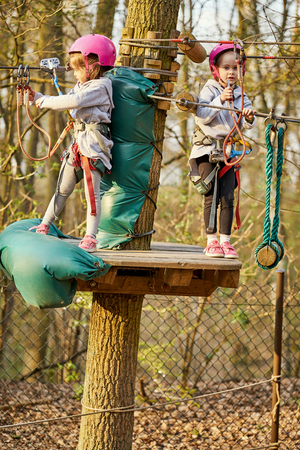 Two adorable little girls in helmet in a rope park in the woods Stock Photo - 125295590