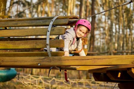 Adorable little girl in helmet in rope park in forest