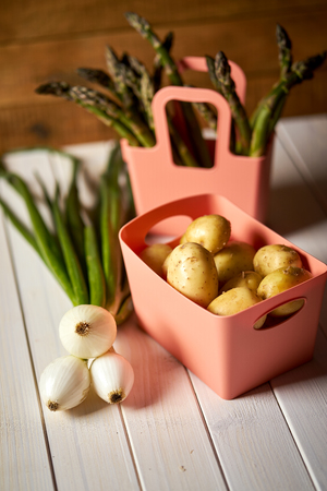 Fresh asparagus potatoes and chives on white  kitchen table