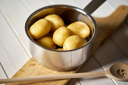 Young potatoes boiled in pot on wooden board on wooden table