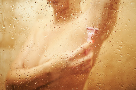 Blurred view on sexy girl in shower behind wet glass that shaves under the armpits. Stok Fotoğraf