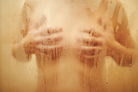 Blurred view on sexy girl in shower behind wet glass with drops.