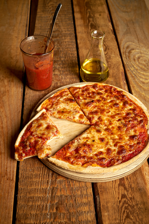 Homemade traditional italian margherita pizza with tomato sauce and olive oil on wooden table Imagens