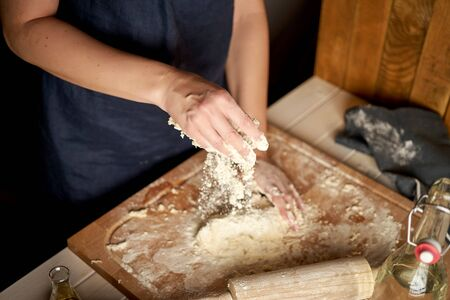 Woman prepares dough on pastry board with flour and rolling pin on wooden table Stockfoto