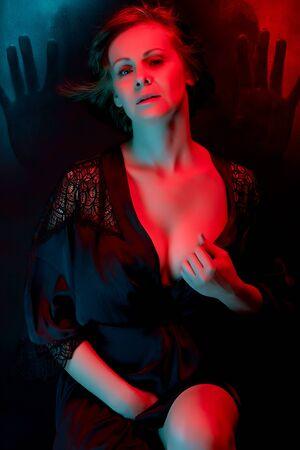 Beautiful attractive woman posing in satin bathrobe in neon light.