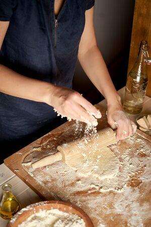 Woman roller dough on pastry board with flour and rolling pin on white table