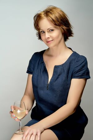 Portrait of attractive woman with glass of wine on gray background