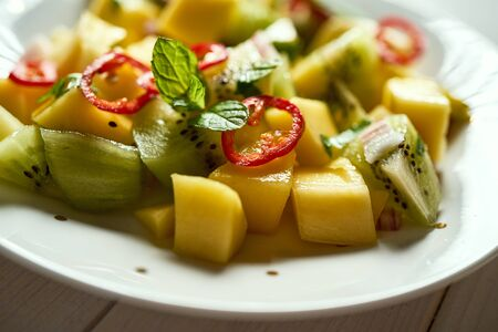 Fresh organic colorful salad with melon on white wooden table Фото со стока