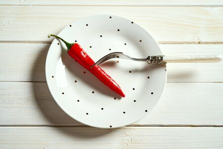 Red chili pepper on white plate on wooden kitchen table