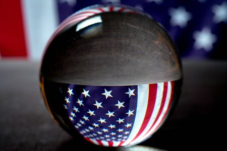 us flag on a black background visible through a glass glossy ball