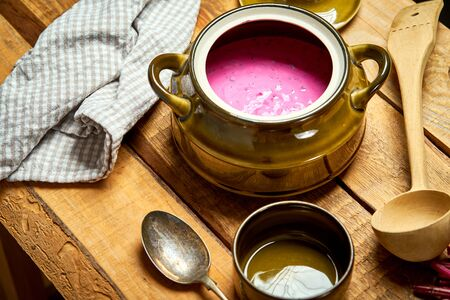 Old vase with  cold beetroot soup and spoon on rustic wooden table Stock Photo