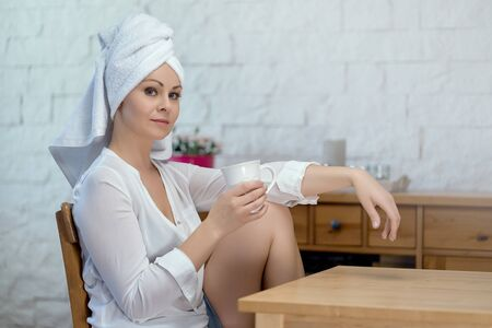 beautiful woman in a bathrobe on her head is drinking coffee from a cup
