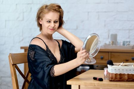 beautiful woman in a black lace bodysuit paints her face with a brush