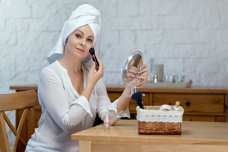 beautiful woman with a towel on her head doing makeup Stock Photo