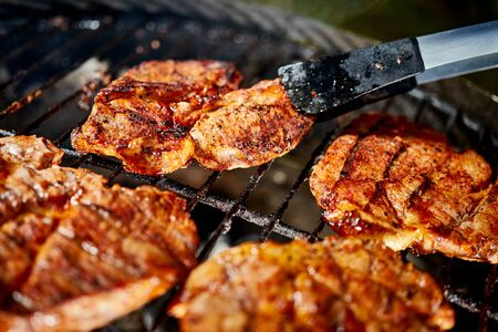 Juicy beef steaks on hot grill with flame on barbecue in garden Stock Photo