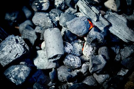 Closeup of glowing coal in metal grill on summer day in garden