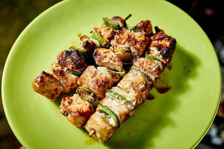 Juicy grilled chicken skewers on green plate on summer day