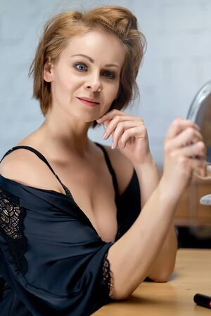 woman in a lace bodysuit and a dressing gown looks at herself in the mirror