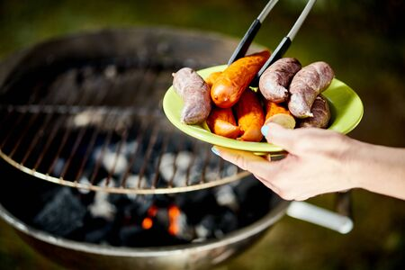 Juicy sausage on hot grill with tongs during summer barbecue