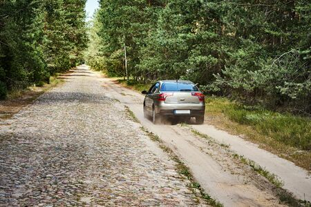 bright car is driving along a gravel road in the forest