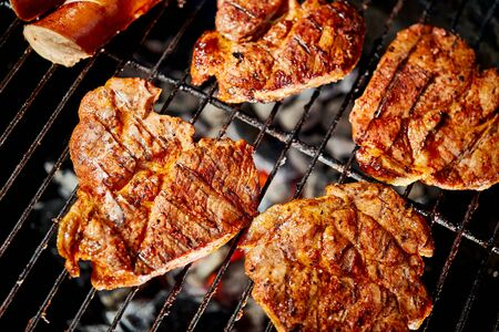 Juicy beef steaks on grill with flame on barbecue in the garden