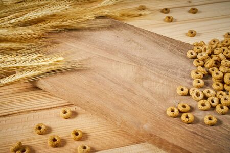 light wooden background with yellow ears of rye and breakfast crunchy 写真素材