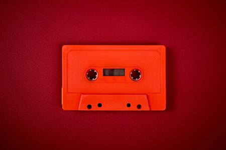 old orange audio cassette on the dark red background