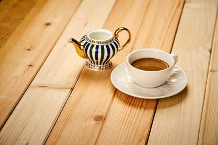 Small cup with aromatic coffee with milk on wooden table