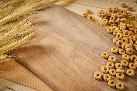 wooden background with yellow ears of rye and breakfast crunchy