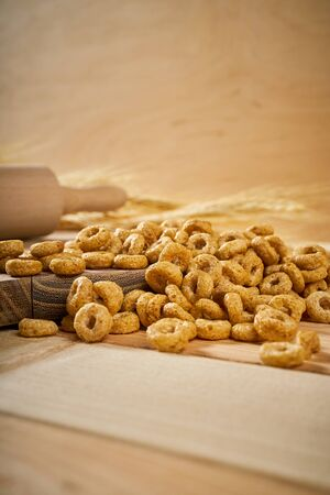 crunchy breakfast on a wooden table with ears of rye and rolling pin