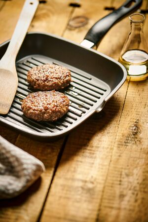 Closeup of two juicy burgers fried on black grill pan