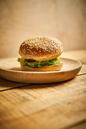 one delicious classic burger on wooden board and black background Stock Photo