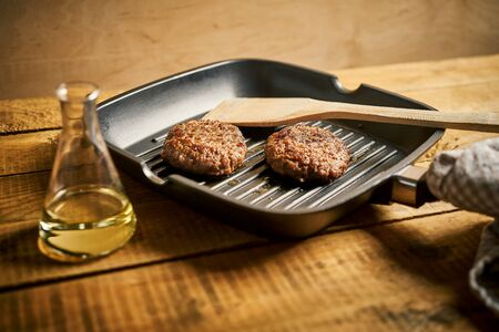 Closeup of juicy burgers fried on black grill pan Stock Photo - 131359404