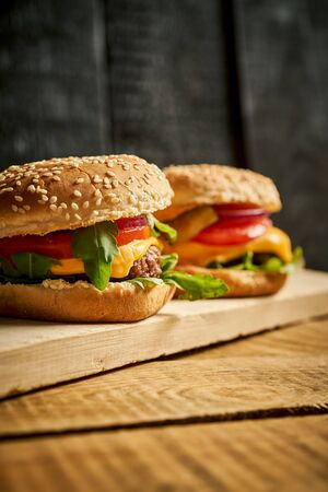 Close up of tasty hamburger on wooden table and black background