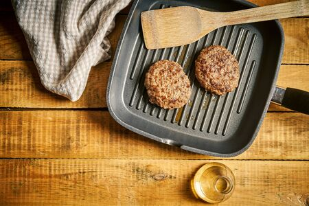 Close up of juicy burgers fried on black grill pan Stock Photo
