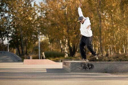 Man with beard in skatepark rides skateboard on warm autumn day Imagens